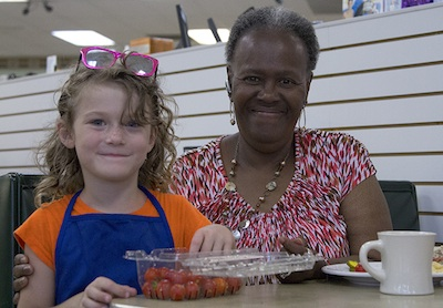 Emily Marie Abraham does a little direct tomato marketing with Gloria Smith at Rayfield's.