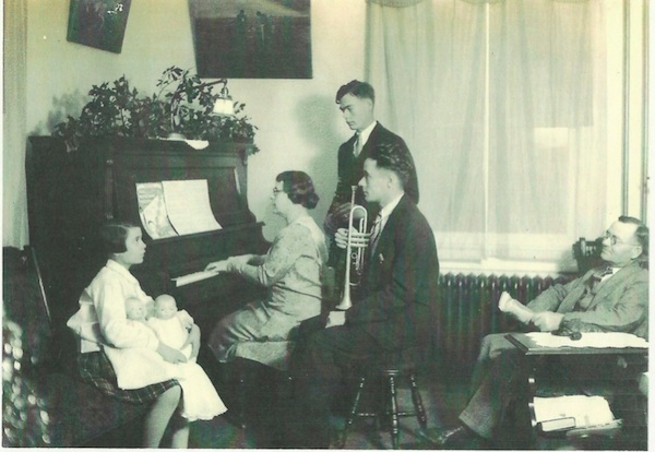 A young Geraldine sits with her dolls while her mother and brothers entertain as her father looks on in approval.